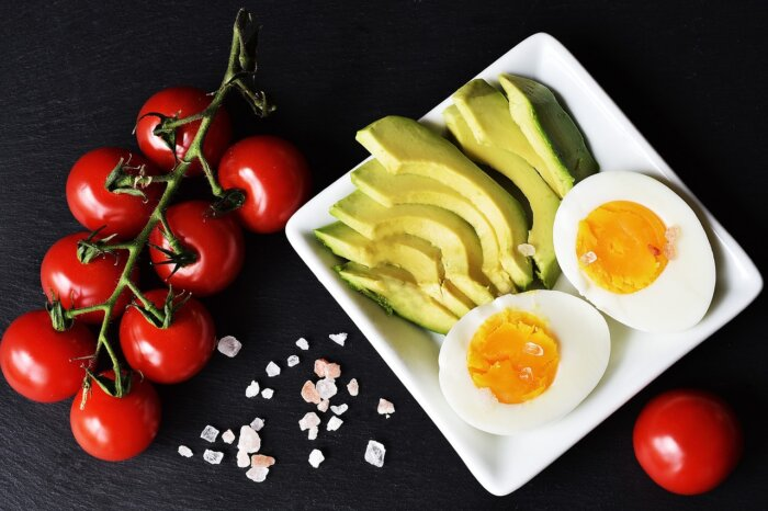Plates of food with egg, tomatoes and green vegetables that you use eat in a Keto diet style